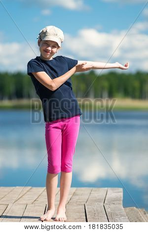 Young girl stands in front of a lake in front of a beautiful nature