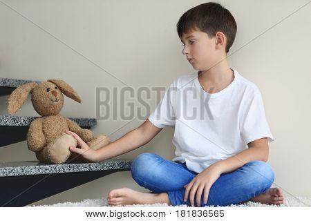 Sad little boy sitting beside stairs