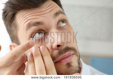 Young man putting contact lenses at home, closeup