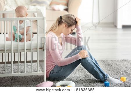 Depressed young woman with cute baby at home