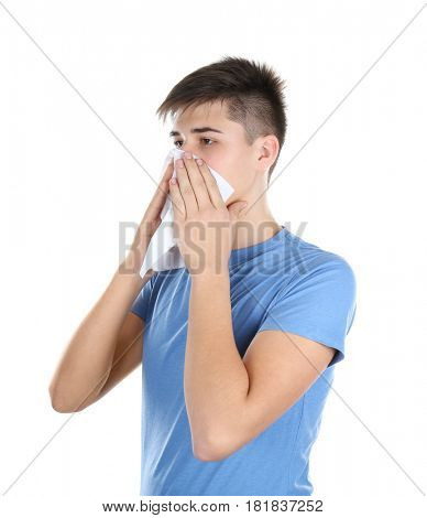 Young man blowing nose on tissue against white background