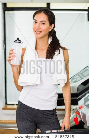 Fitness woman drinking water while exercising on treadmill at the gym.