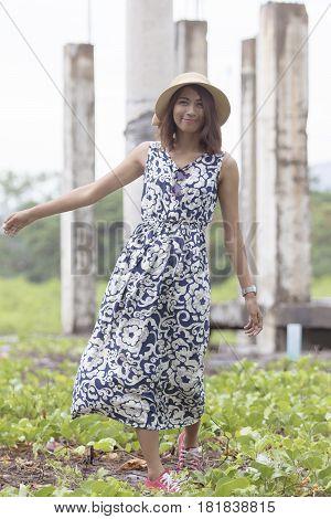 portrait of beautiful fashion shot of asian tan skin younger woman wearing straw hat standing outdoor
