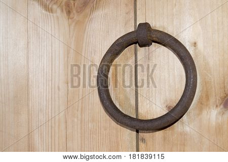 A wooden door with a ring in rural areas.