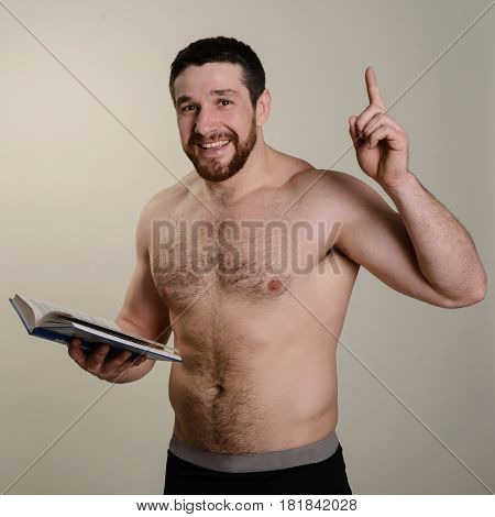 Brutal cheerful bearded athlete with a book is pointing his finger at the top.