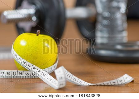 Fresh apple and centimeter close-up in the gym on the floor against a dumbbell background