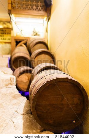 The side close-up view of the barrels lying near the walls on the brick floor