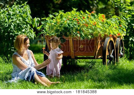 Cute baby girl with mother in a garden next to a decorative flower wooden wagon. Child holding a flower.