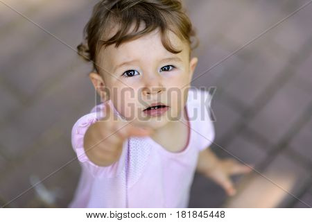 The one-year-old child looking up and points his finger at the camera. Cute baby girl is tired to play and asks for the hand.