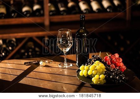 Set of fruits, wine glass and bottle placed on a wooden table in a wine vault.
