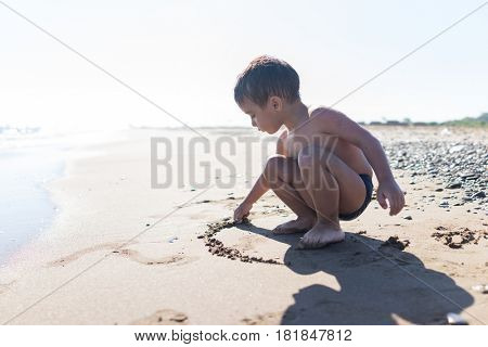 Little cute child is playing in sand on the sea beach in summer.
