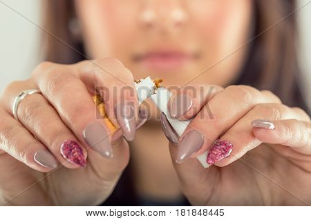 Quit smoking.Woman hands breaking bunch of cigarette.