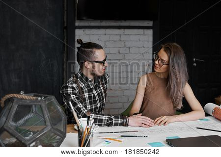 Lovely couple of young student working on diploma project and prepare presentation in college. Man hold woman hand at the job. Office novel concept. Girl and guy look each other in moder interior.