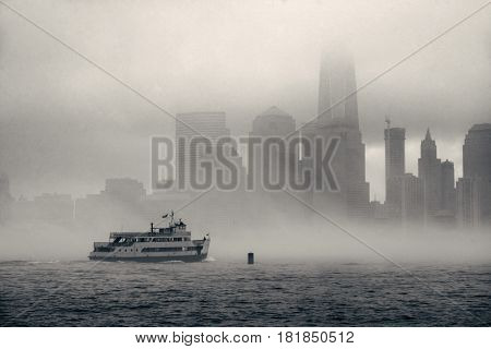 Downtown Manhattan skyscraper and boat in river in a foggy day in New York City.