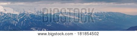 Panoramic view of the Caucasus mountains in the cloudy winter weather at Rosa Peak