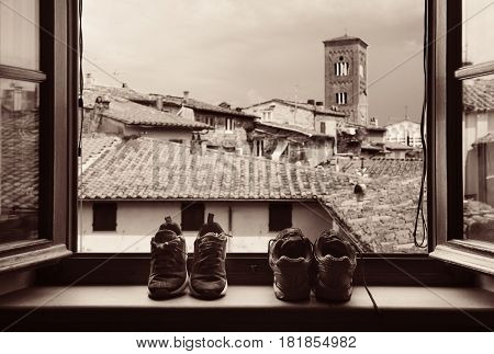 Shoes in front of window in Medieval Town Lucca with historic buildings in Italy.