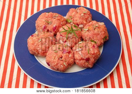 some raw meatballs with onions and rosemary