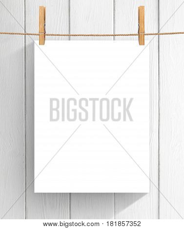 Empty sheet of paper hanging on the clothesline over wooden background. Mock up for your project with copy space
