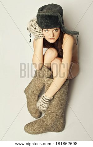 Naked girl in boots and a fur hat