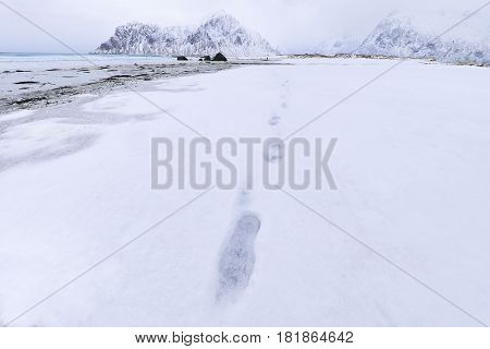 Footprints of a man on the snow of a Norwegian beach.