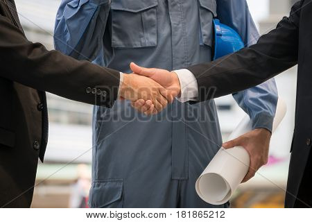 Businessmen Handshake With Engineer Behind