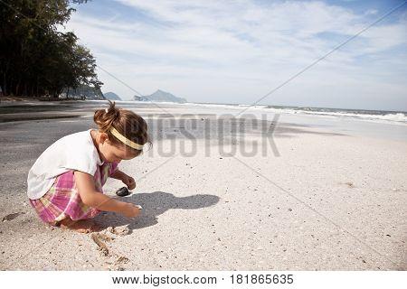 Asian Girl building sandcastle on the beach