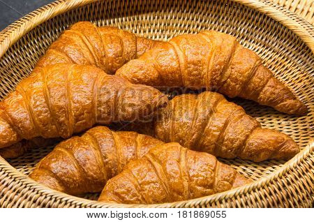 delicious golden croissants in a straw basket