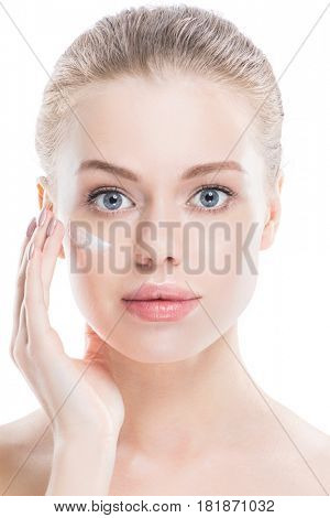 Beautiful young woman with cream on clean fresh face skin close up isolated on white background