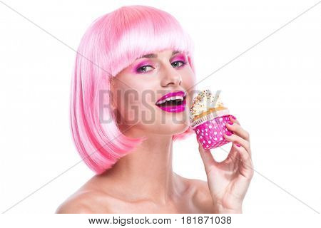 Portrait of girl with glamour make-up and pink hair ready to eat a cake isolated on white background