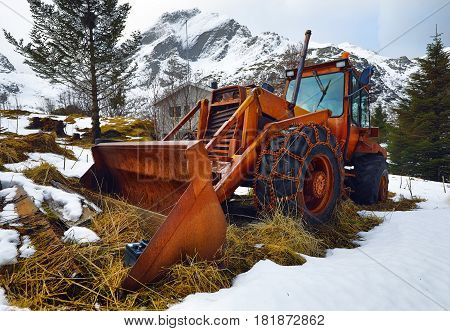 Old rusty Norwegian tractor with wheel chains.