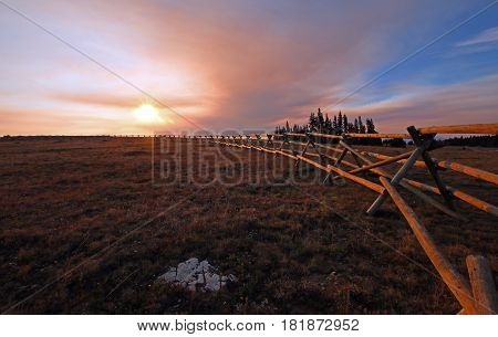 Split Rail Fence at sunrise above Lost Water Canyon in the Pryor Mountains Wild Horse range on the Montana Wyoming state line USA