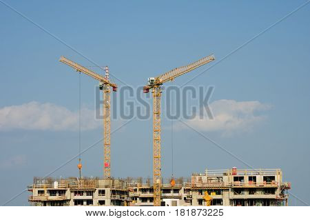 Two Large Yellow Cranes On An Apartment House Construction Site