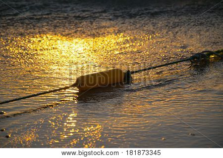 Float buoy and ropes on the beach, sunset