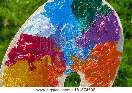 Color palette with multi-colored paints on the grass