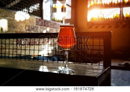 Glass on a thin stalk of crafted ale on wooden table in beer bar
