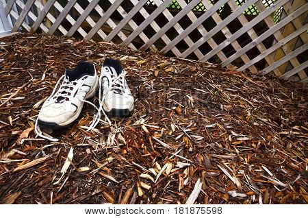 garden shoes footwear in the mulch with lattice fence