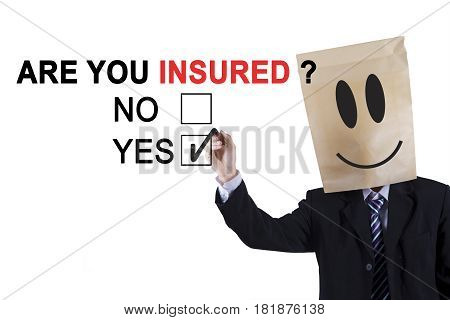 Male worker wearing cardboard on his head and holding a pen while agreeing about a question of are you insured