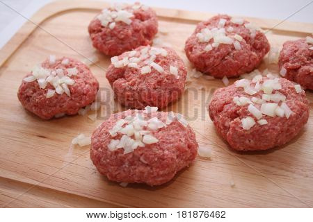 some raw meatballs of minced meat with onions