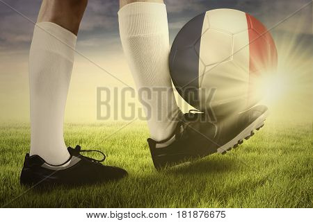 Close up of a ball with flag of France on the foot of football player at the field. Concept of european football championship 2016