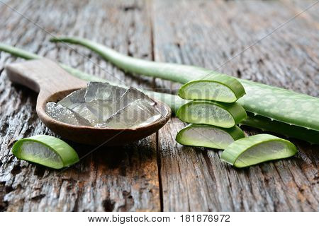 aloe gel on wooden spoon with aloe sliced on wooden table.