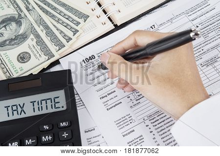 Hands of businessman are filing tax forms with dollar money and text of tax time on the calculator