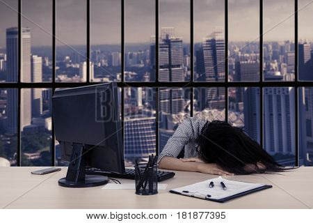 Overworked businesswoman with a computer and paperwork while sleeping on the desk