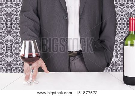 Close up on elegant man serving red wine.