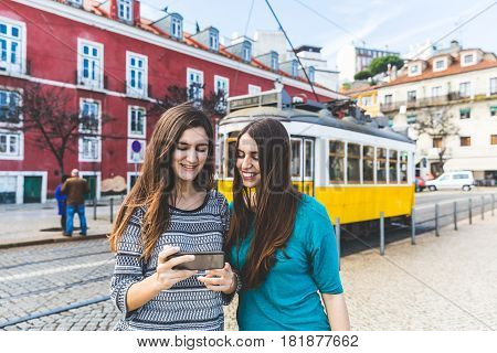 Girls With Smartphone In Lisbon, Tram On Background