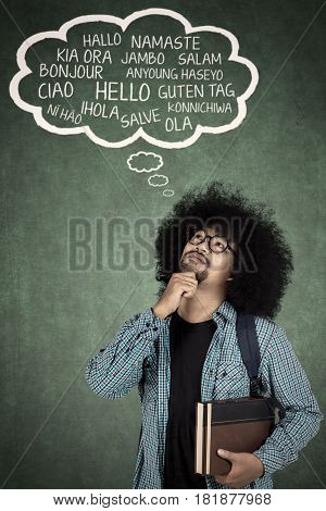 College student thinking foreign language with cloud speech over his head while holding a book