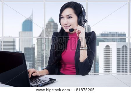 Portrait of beautiful customer service operator working in the office with laptop and headphones
