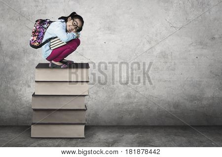 Cute female elementary school student squat on a stack of book while carrying backpack and book shot with grey background
