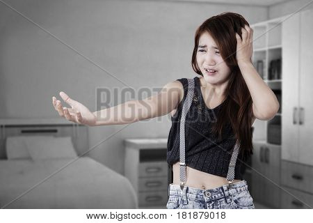 Portrait of casual teenage girl standing in the bedroom and looks scared when looking at her hand