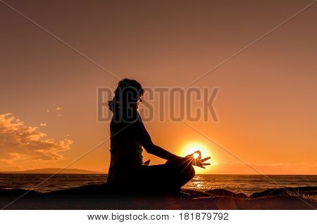 a woman practicing yoga on a maui beach silhouetted at sunset