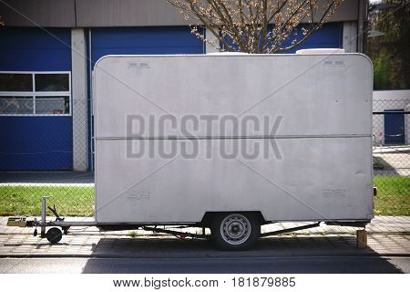 A car trailer with canopy and transport of small objects tools and materials parks at the roadside.